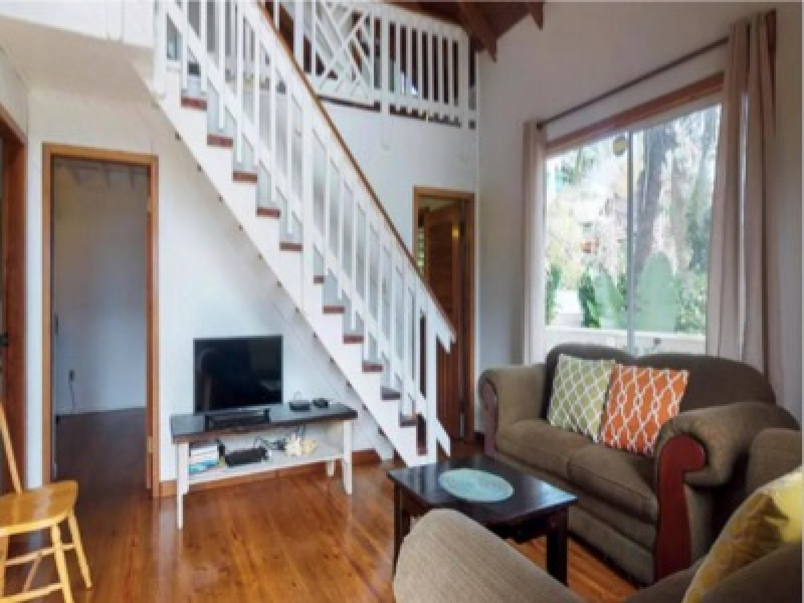 Comfortable lounge area with stairs leading to the spacious loft area.