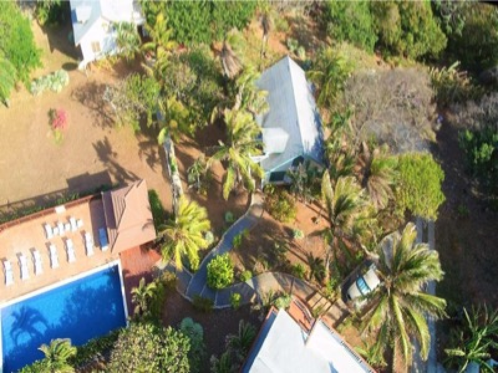 The home, right next to the pool, with meandering pathway through tropical greenery.