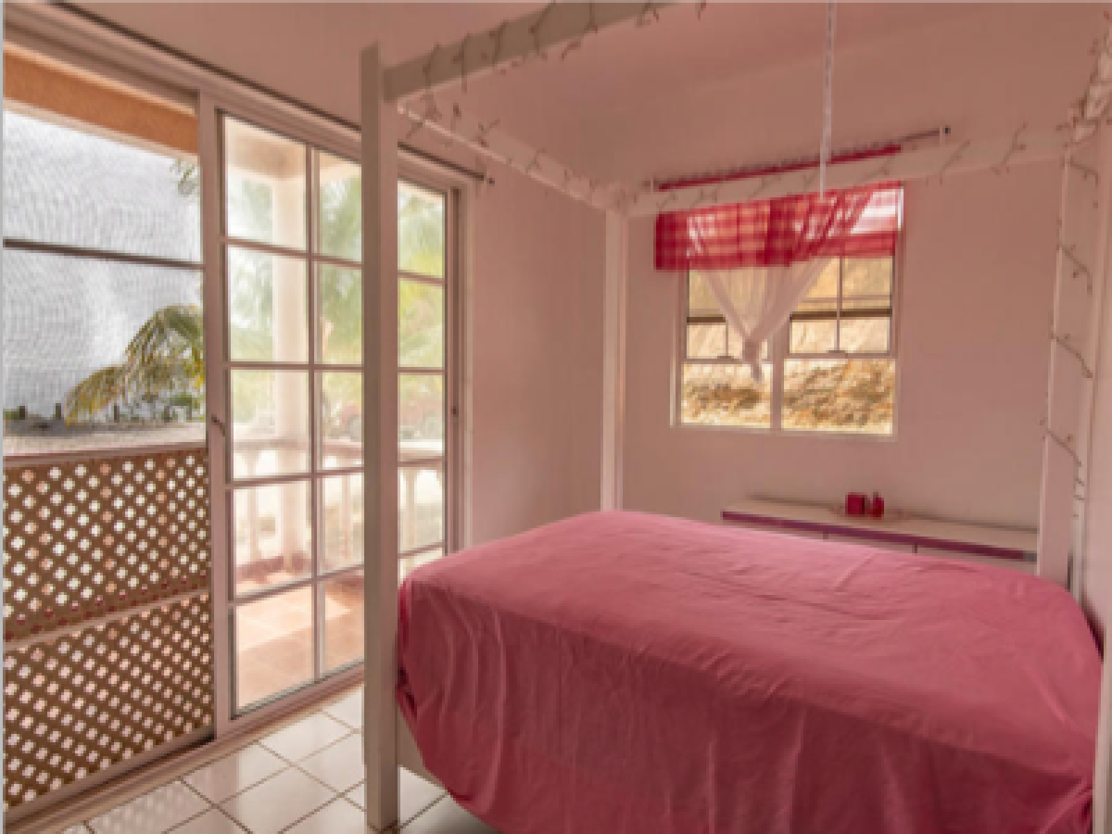First floor guest bedroom with four poster bed and balcony to enjoy the tropical breezes